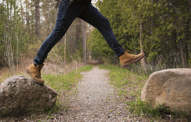 Low section of man jumping over rocks in forest