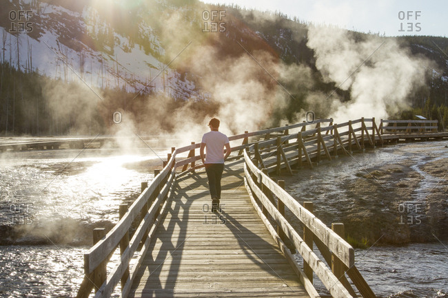 Rear view of hiker walking on boardwalk by hot springs at Yellowstone National Park
