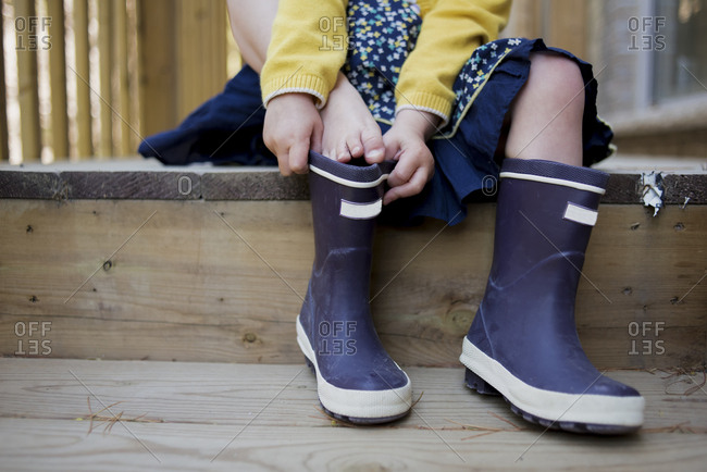 Low section of girl putting on rubber boots