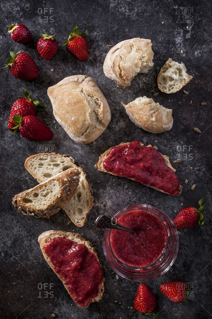 Overhead view of bread with strawberry jam on slate