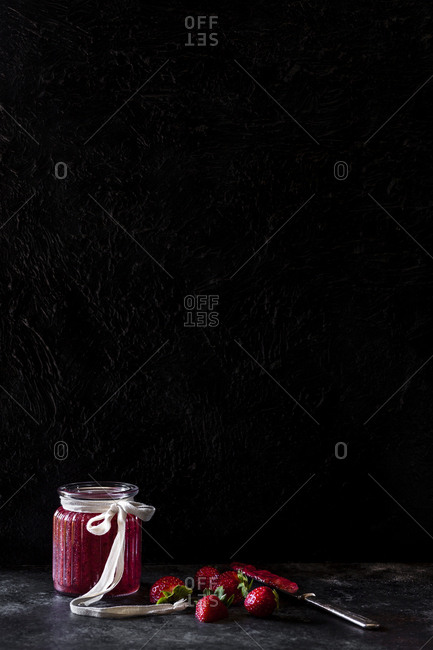 Jam with strawberries on slate against wall