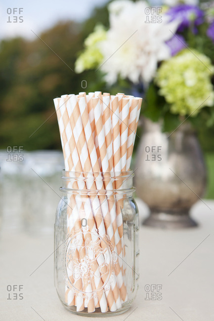 Striped straws in a jar as part of an outdoor wedding table setting