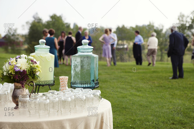 Drinks table and guests at an outdoor wedding in the country