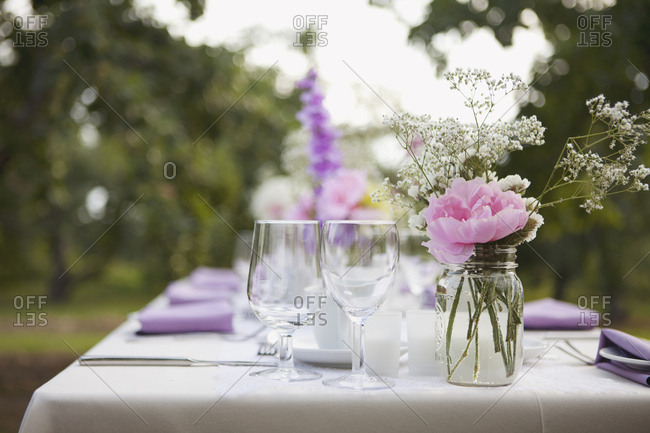 Bouquet in a mason jar and table set for an outdoor wedding in an orchard