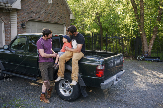 Two mid-adult men playing with toddler by a truck