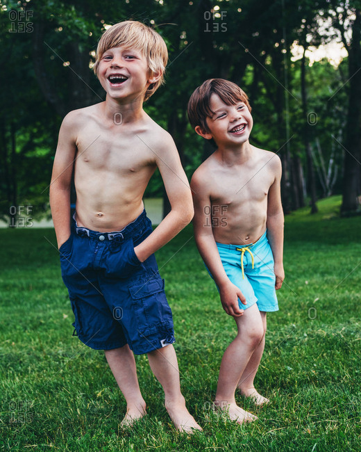 Two young boys laughing outside in the back yard in the summer
