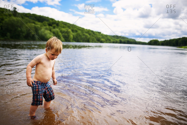 Young toddler boy playing on a river beach