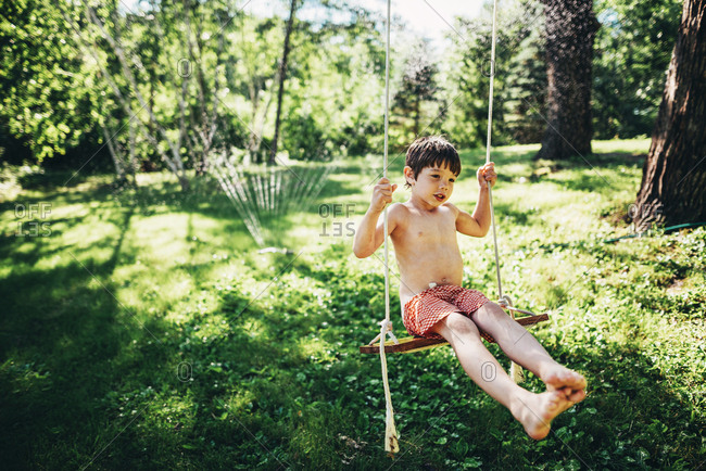 Young boy on backyard swing playing in a sprinkler