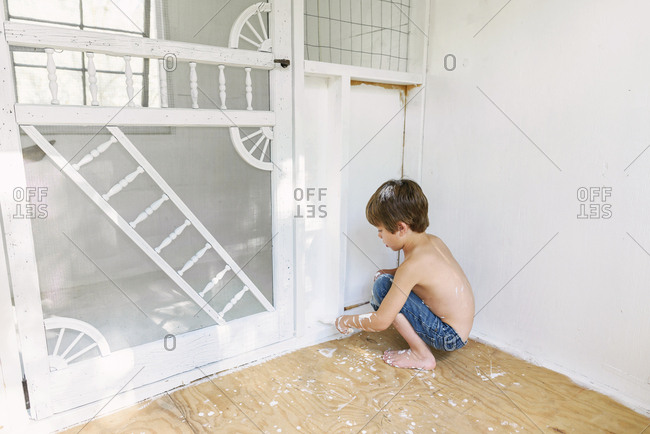 A young boy painting a chicken coop