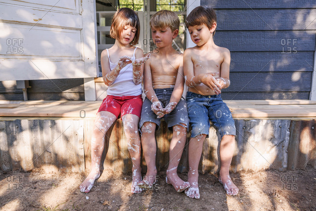 Three young children painting a chicken coop