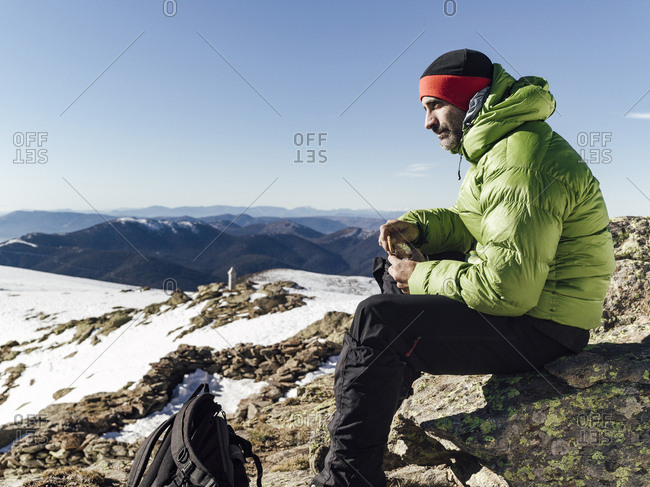 Alpinist seated on a rock having a break while looking the landscape  in Pe�alara, Madrid, Spain