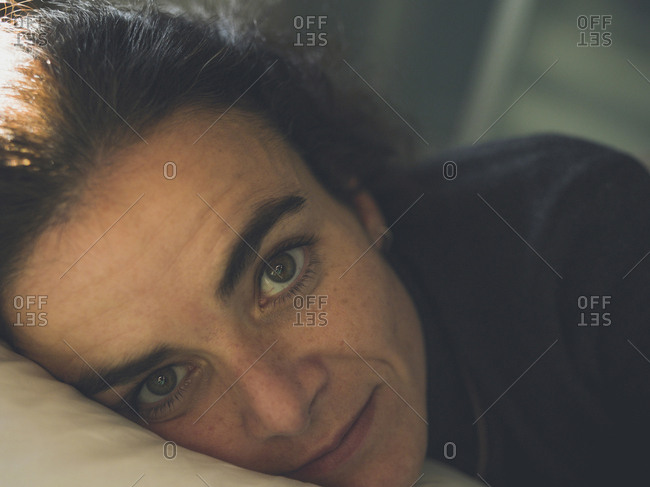 Middle aged woman relaxed with head on a pillow in a bedroom in Madrid, Spain