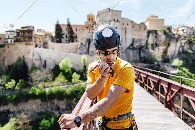 Urban climber on top of a bridge talking on a walkie to organize an activity in Puente de San Pablo, Cuenca, Spain