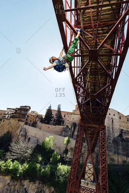 Urban climber hanging from a bridge doing a risk activity in Puente de San Lucas, Cuenca, Spain