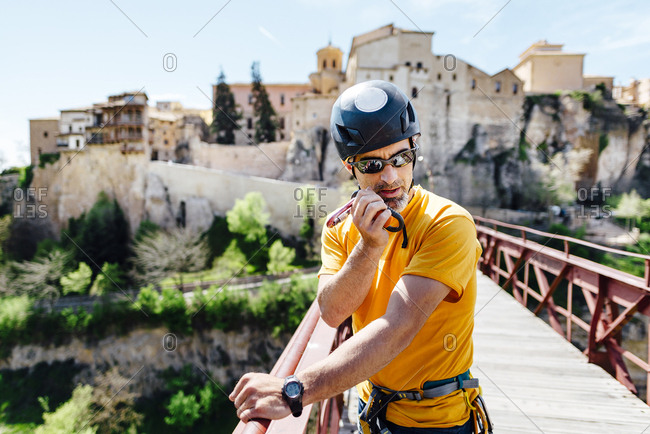 Urban climber on top of a bridge talking on a walkie to organize an activity in Puente de San Pablo, Cuenca, Spain