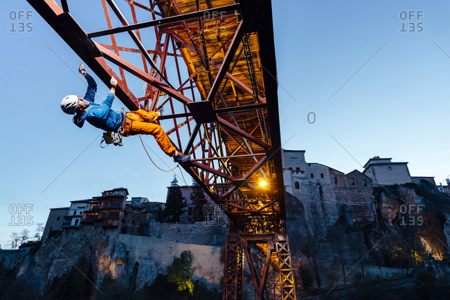 Urban climber hanging from a bridge doing a risk activity at dusk in Puente de San Lucas, Cuenca, Spain