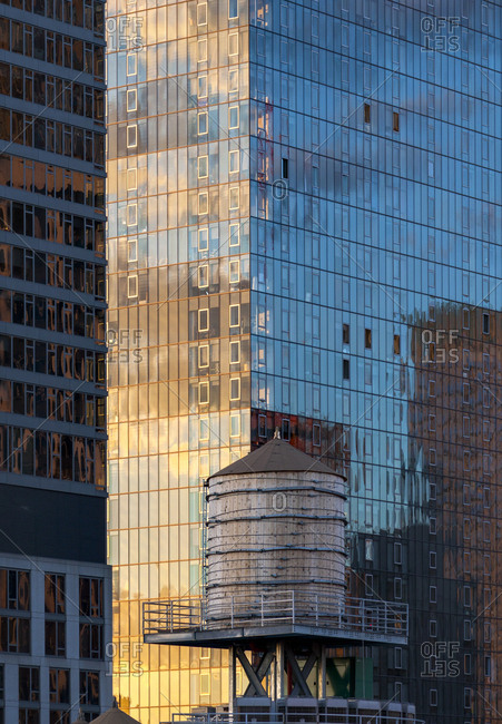 The sun reflects on the side of a glass skyscraper