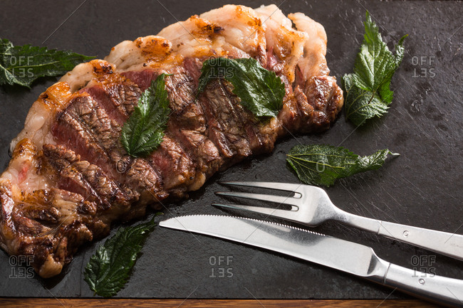 Grilled steak with fresh herbs, knife and fork
