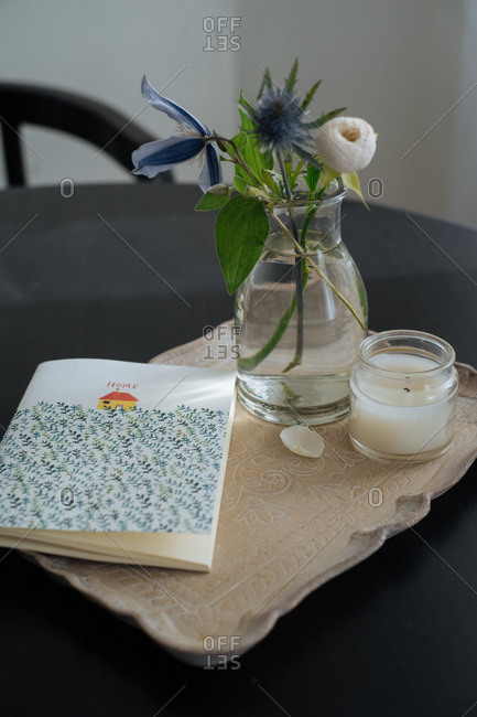 Journal, flower bouquet and candle on a stone serving tray