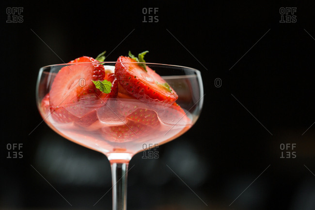 Sliced strawberries  and mint served in a cocktail glass