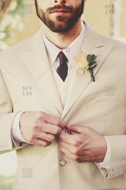 Groom getting ready for wedding butting up jacket