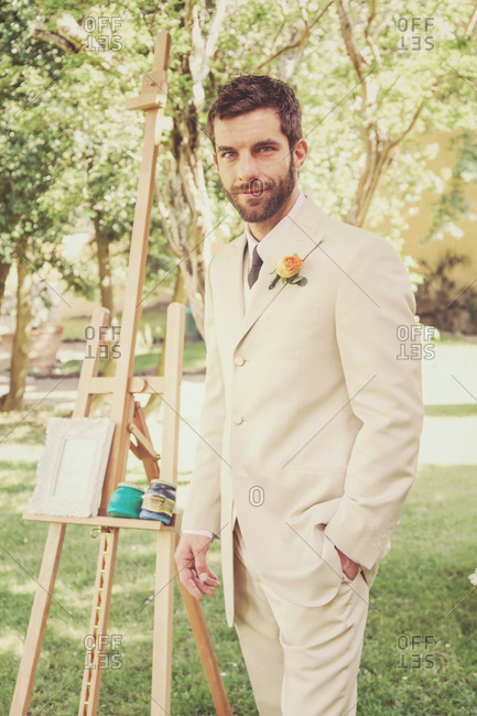 Portrait of groom posing next to an easel