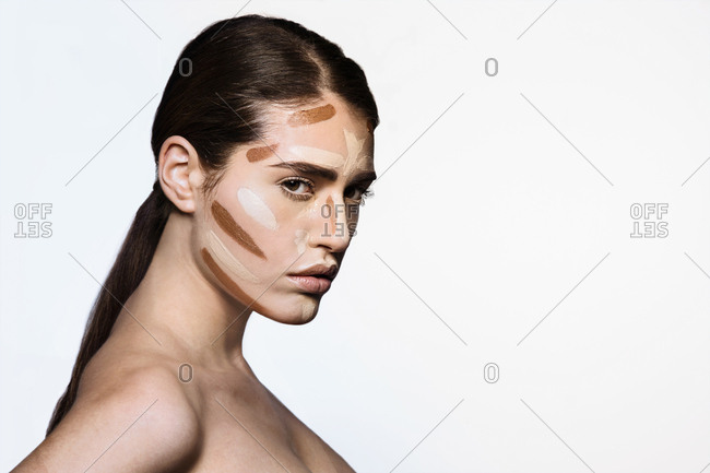 Beautiful young woman with base make up applied on face  for contouring technique to sculpt her features profile looking at camera