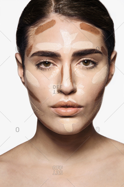 Beautiful young woman with base make up applied on face  for contouring technique to sculpt her features looking at camera