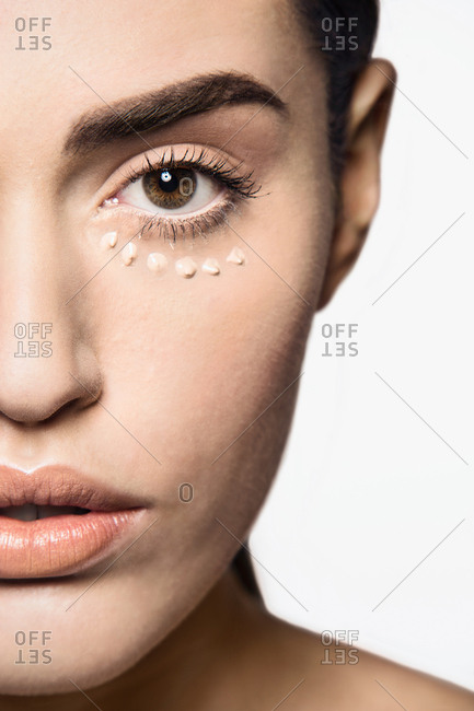 Beautiful young woman with base make up applied on face  for contouring technique to sculpt her features, with eyes closed
