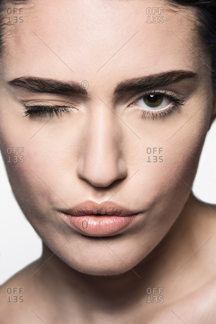 Close up of young woman's face winking at camera