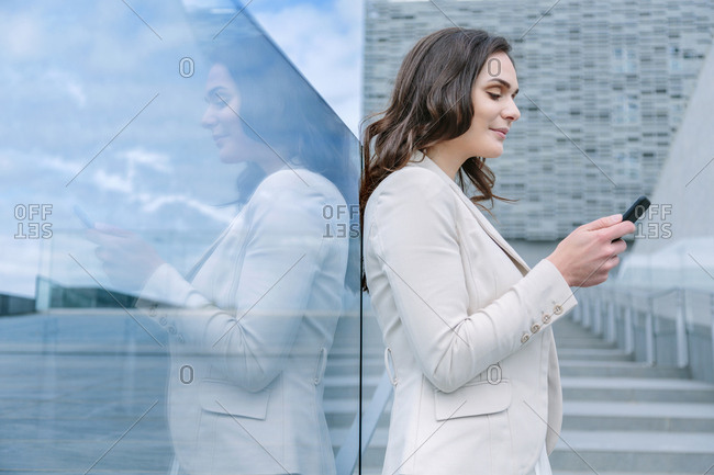 Young woman leaning on a window using her phone