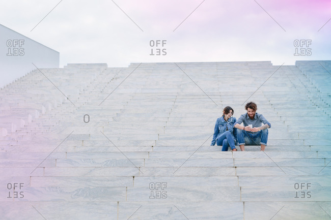 Young couple sitting in a big amphitheater