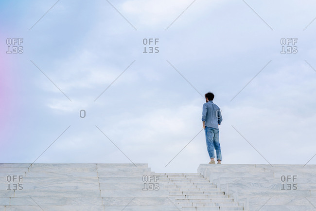 Young man stands alone on top of some steps