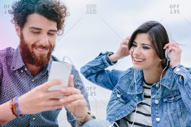 Happy young couple listen to music together