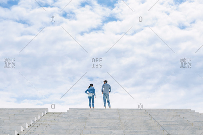 A couple stand high on top of some steps