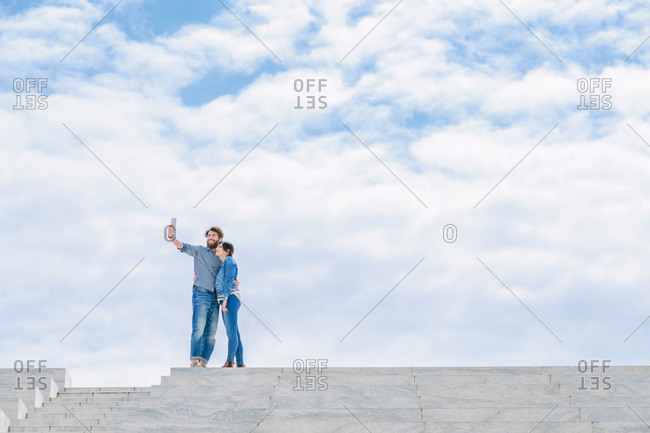 Young couple stand high up taking a selfie
