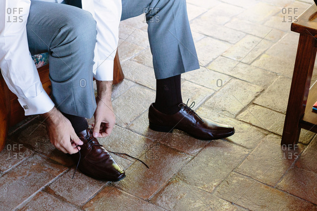 Groom tidying up shoes before ceremony