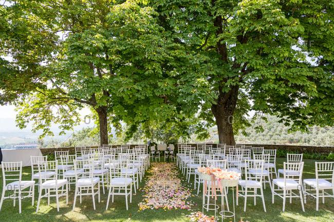 Wedding ceremony setting in Italian garden under tress