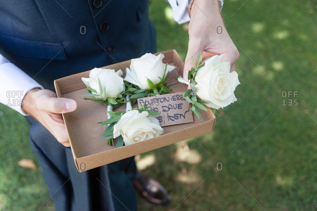 Best man carrying box with boutonnieres at wedding