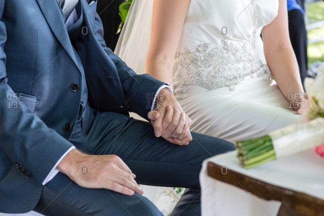 Bride and groom holding hand during wedding ceremony