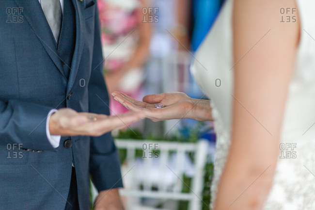 Close up of bride and groom holding wedding rings in the palm of their hands