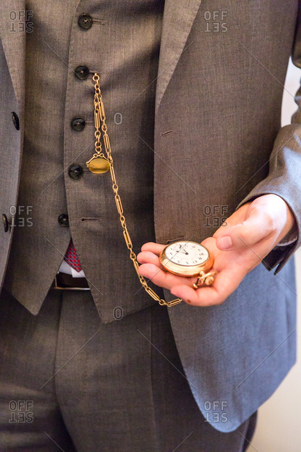 close up of groom checking time before wedding ceremony