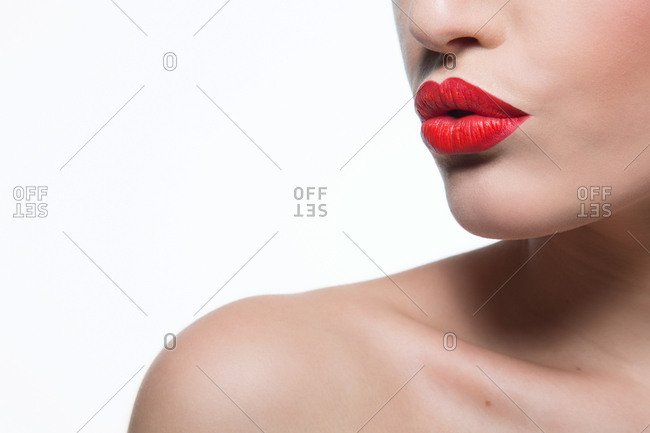 Close up of young woman with red lips and bare shoulder blowing a kiss with a  pout