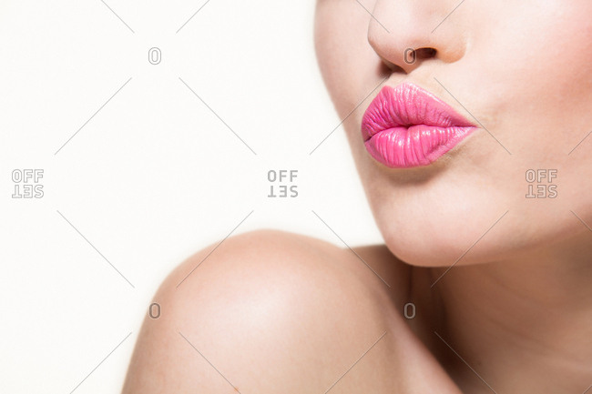 Close up of young woman beautiful mouth with bright pink lipstick blowing kiss