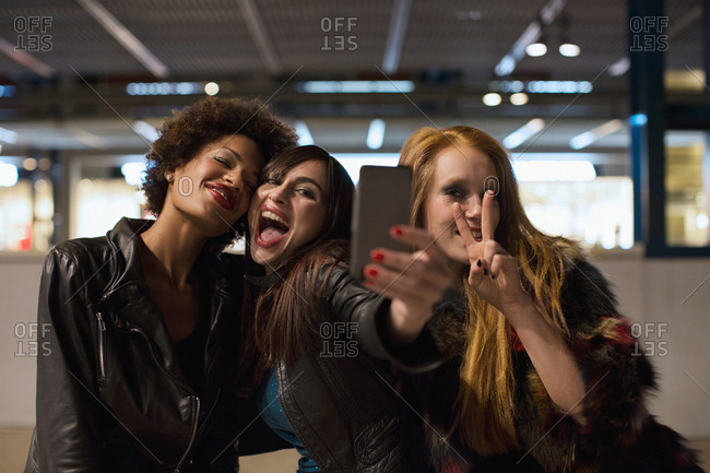 Three cool girl friends taking selfie on night out celebrating