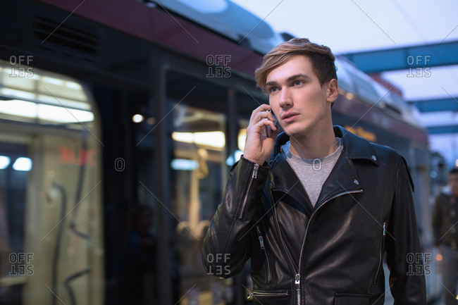 Cool young man talking on mobile on the go near train station