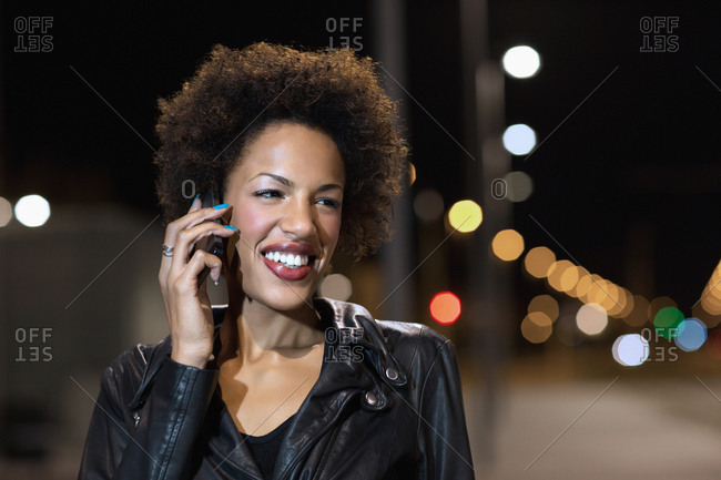 Happy young woman with mobile phone out at night near train platform laughing