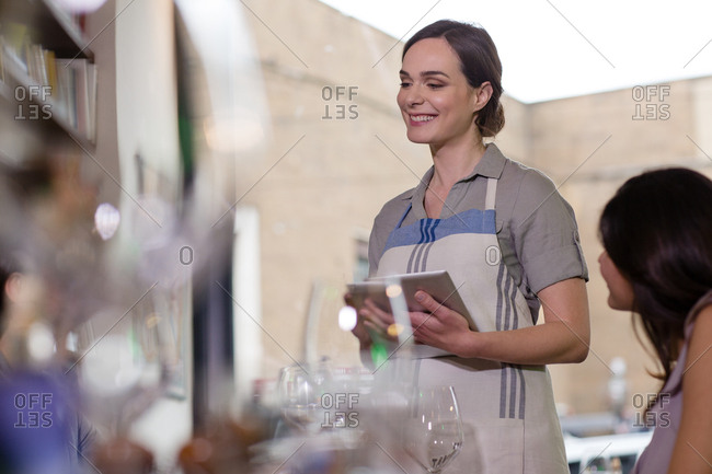 Smiling happy waitress holding a tablet taking orders
