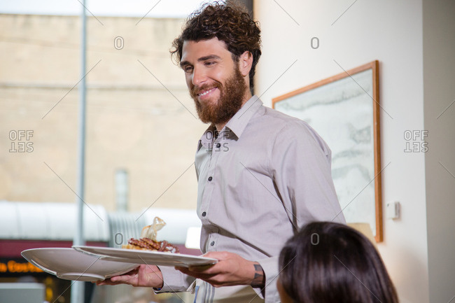 Happy waiter bringing out food smiling