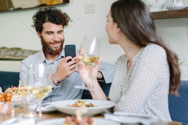 Young man taking photo of woman during lunch celebration